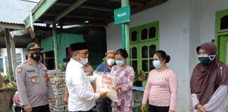 Ketua DPRD Bolsel dan Kapolsek Pinolosian Salurkan Bantuan Beras PPKM kepada Warga Desa Linawan